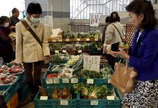 Compradores miran vegetales en una verdulería en el distrito comercial de Ginza, en Tokio. Japón. 31 de marzo de 2016. La confianza de los grandes fabricantes de Japón cayó a su nivel más bajo en casi tres años y se espera que empeore en el próximo trimestre, mostró el viernes una encuesta del banco central, lo que aumenta la presión sobre el primer ministro, Shinzo Abe, y el Banco de Japón para que apoyen a la economía. REUTERS/Yuya Shino