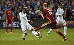 Sporting KC defender soni Mustivar (93) shoots the ball on goal against Real Salt Lake defender Justen Glad (15) during the second half at Children's Mercy Park. Peter G. Aiken-USA TODAY Sports