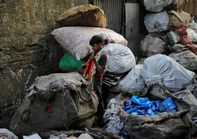 A boy sews up a sack of plastic trash outside a recycling factory in Dharavi, one of Asia's largest slums, in Mumbai in this file photo dated December 10, 2012. REUTERS/Danish Siddiqui