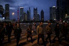 La actividad del sector de servicios de China se fortaleció en marzo, pero el empleo cayó por primera vez en más de dos años y medio, mostró el miércoles un sondeo privado, lo que envió señales dispares sobre la salud de un sector con el que Pekín cuenta para que compense la debilidad de las manufacturas. En esta imagen se ve a gente cruzando una carretera a su salida del trabajo en el distrito financiero de Pudong en Shanghai, el 15 de marzo de 2016. REUTERS/Aly Song