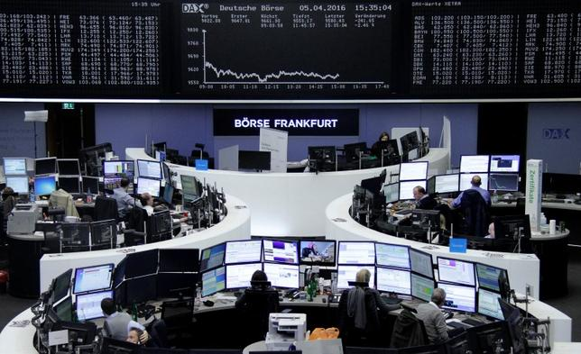 Traders work at their desks in front of the German share price index, DAX board, at the stock exchange in Frankfurt, Germany, April 5, 2016. REUTERS/Staff
