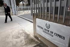 Мужчина у главного входа в здание ЦБ Кипра в Никосии. 22 февраля 2013 года. Кипр усиливает требования к коммерческим банкам и посредникам, касающиеся личности их клиентов, спустя несколько дней после того, как была обнародована масштабная утечка данных, описывающих схемы, которые использовались богачами со всего мира для размещения доходов в налоговых гаванях. REUTERS/Yorgos Karahalis
