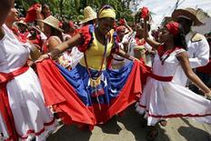 Женщина в платье цветов флага Венесуэлы танцует во время религиозного праздника в городе Курьепе. 24 июня 2015 года. Президент Венесуэлы Николас Мадуро объявил все пятницы в ближайшие два месяца выходными днями ради экономии электричества в страдающей в последнее время от частых отключений энергии стране ОПЕК. REUTERS/Jorge Dan Lopez