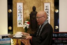 Shokyo Miura, a Buddhist monk and one of the on-site priests, carries cups of coffee past a statue of Buddha at Tera Cafe in Tokyo, Japan, April 1, 2016. REUTERS/Yuya Shino