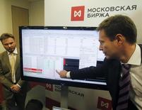 Сотрудники Московской фондовой биржи во время торгов.  Российский фондовый рынок завершает неделю в плюсе, поддерживаемый ожиданиями переговоров крупнейших мировых нефтедобывающих стран в Дохе, а среди популярных у игроков бумаг все еще остаются акции электроэнергетики. REUTERS/Maxim Shemetov