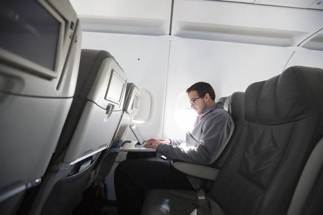 A man uses his laptop  while on a special JetBlue media flight out of John F. Kennedy International Airport in New York December 11, 2013.   REUTERS/Lucas Jackson