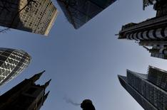 Los bancos de inversión deben hacer más para fomentar la competencia y el trato justo de los clientes, dijo el regulador financiero de Reino Unido, que propone cambios para ayudar a las empresas a tomar decisiones informadas sobre los bancos que utilizan. En la imagen, un trabajador de la  City camina entre los rascacielos del distrito financiero de Londres, el 16 de diciembre de 2014. REUTERS/Toby Melville