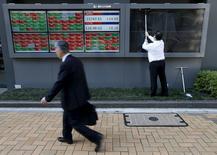 Un hombre limpia las pantallas de unos paneles electrónicos que muestras el índice Nikkei y la tasa cambiaria entre el yen y el dólar estadounidense, afuera de una correduría en Tokio, Japón. 6 de abril de 2016. Las bolsas de Asia operaban el jueves en máximos en más de cuatro meses y las monedas de la región retrocedían en medio de las esperanzas de que más bancos centrales anunciarán una relajación de su política monetaria en los próximos meses. REUTERS/Issei Kato
