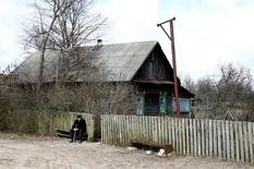 Ivan Shamyanok, 90, sits in front of his house in the village of Tulgovichi, near the exclusion zone around the Chernobyl nuclear reactor, Belarus April 2, 2016.  REUTERS/Vasily Fedosenko