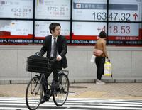Un hombre en bicicleta pasa frente a un tablero electrónico que muestra el índice Nikkei de Japón, afuera de una correduría en Tokio, Japón. 13 de abril de 2016. Las bolsas de Asia subían levemente el viernes en medio de la cautela antes de una reunión de los productores de crudo, y luego de que los mercados de la región tomaron con calma unos datos de crecimiento en China relativamente optimistas. REUTERS/Toru Hanai