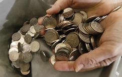 Кассир пересчитывает рублевые монеты.  Рубль падает утром понедельника на фоне обвала нефтяных котировок после неудачных переговоров крупнейших стран-производителей о заморозке добычи. REUTERS/Ilya Naymushin