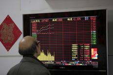 Un inversor mira una pantalla que muestra información bursátil en una correduría en Shanghái, China, 14 de marzo de 2016. Las acciones de China cayeron el lunes, en línea con los mercados regionales, debido a que un desplome de los precios del crudo golpeó la confianza de los inversores. REUTERS/Aly Song