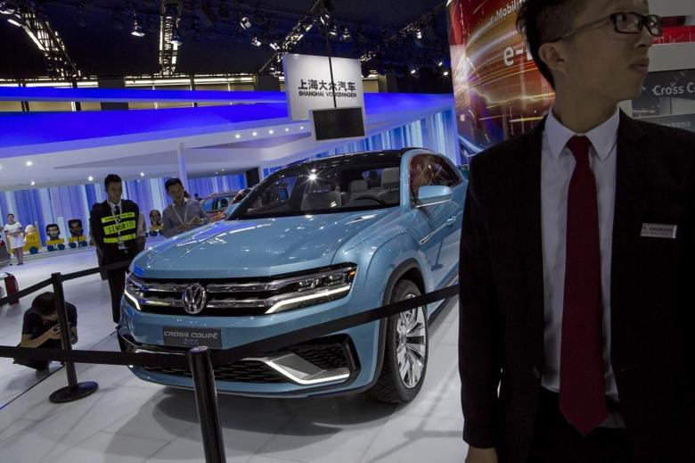 A staff stands next to a Volkswagen Cross Coupe GTE hybrid SUV at the 13th China (Guangzhou) International Automobile Exhibition in Guangzhou, China November 20, 2015. REUTERS/Tyrone Siu