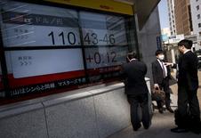 Personas miran un tablero electrónico que muestra información bursátil, en Tokio, Japón. 6 de abril de 2016. Las bolsas de Asia y el dólar caían el lunes luego de que los inversores recogieron ganancias de los recientes avances de la moneda antes de las reuniones de los bancos centrales de Estados Unidos y Japón esta semana. REUTERS/Issei Kato