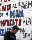 """Человек проходит мимо граффити, гласящих: """"Нет выплате долгов!"""" в Буэнос-Айресе 22 апреля 2016 года. Возвращение Аргентины на прошлой неделе на мировые рынки капитала стало финальным аккордом изматывающего 14-летнего дрейфа латиноамериканской страны от исторического дефолта, по волнам судебной системы США. REUTERS/Marcos Brindicci"""