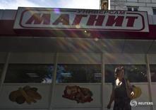 Женщина у  магазина Магнит на окраине Москвы 24 июля 2012 года.  Акции Магнита в понедельник испытали рекордное для этого года внутридневное падение по вине снижения прибыли и рентабельности, а бумаги Лукойла снизились, хоть и скромнее, после объявления новой дивидендной политики. REUTERS/Maxim Shemetov