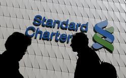 Люди проходят мимо логотипа Standard Chartered в Гонконге 8 января 2015 года. Standard Chartered сообщил о падении прибыли в первые три месяца текущего года примерно на 59 процентов в годовом выражении, виной чему стал рост отчислений на покрытие плохих кредитов, а также слабость мировой конъюнктуры. REUTERS/Bobby Yip/File Photo