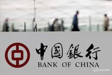 Пешеходы за логотипом Bank of China в Пекине 28 марта 2016 года. Bank of China Ltd (BoC), четвертый по объему активов кредитор Китая, во вторник отчитался о 1,7-процентном росте чистой прибыли в первом квартале, несмотря на негативное воздействие плохих кредитов. REUTERS/Kim Kyung-Hoon/File photo