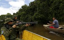 A gold prospector is detained by agents of Brazil's environmental agency on the Uraricoera River during an operation against illegal gold mining on indigenous land, in the heart of the Amazon rainforest, in Roraima state, Brazil April 15, 2016.  REUTERS/Bruno Kelly