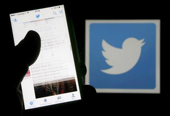 A man reads tweets on his phone in front of a displayed Twitter logo in Bordeaux, southwestern France, March 10, 2016. REUTERS/Regis Duvignau/Illustration/File Photo