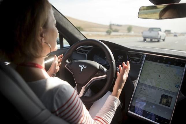 4月26日、自動車メーカーやハイテク企業は、自動運転車が普及すれば交通事故が減ってバラ色の未来が訪れると夢見ているが、全員が勝ち組になるとは期待できない。写真は、「オートパイロット」機能で運転中の米テスラの「モデルS」セダン。カリフォルニア州で昨年10月撮影(2016年 ロイター/Beck Diefenbach)