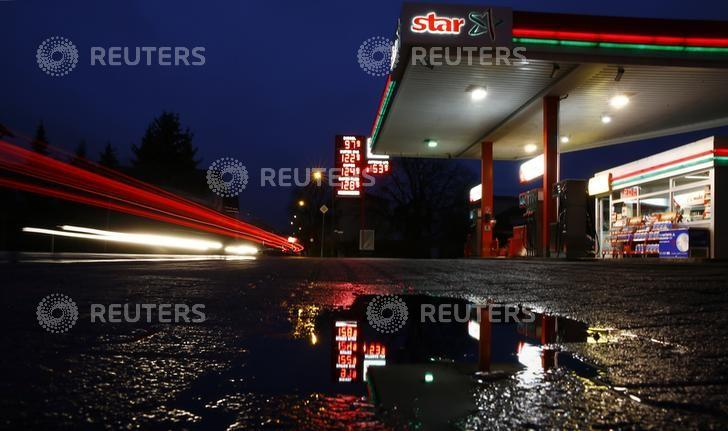 The price indicator of a small gas station is reflected in a puddle on a rainy morning in the village of Klein-Auheim, Hanau,  Germany, early morning February 1, 2016. Due to low oil prices one liter of unleaded petrol at this Star gas station was 1.44 $ early morning February 1, 2016. REUTERS/Kai Pfaffenbach