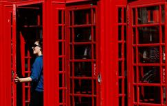 A woman poses in the door of a row  traditional red telephone boxes in central London August 11, 2013.   REUTERS/Luke MacGregor