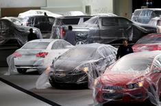 Trabajadores cubren los autos con plástico protector, mientras preparan una exhibición de General Motors a los medios, en Detroit, Michigan, Estados Unidos. 11 de enero de 2014. Las ventas de automóviles en abril en Estados Unidos se encaminaban a un nuevo máximo para el mes el martes, aunque las acciones de la industria se veían presionadas por la preocupación de que el sector esté llegando a un pico. REUTERS/Rebecca Cook/File Photo