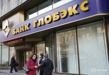 Люди проходят мимо офиса банка Глобэкс в Москве 16 октября 2008 года. Дочерний банк госкорпорации Внешэкономбанк - Глобэкс - недосоздал резервы под обесценение кредитов на 14,6 миллиарда рублей и не списал активы на 1,2 миллиарда рублей по состоянию на 1 января 2016 года, следует из аудиторского заключения Ernst & Young к отчетности банка по международным стандартам за 2015 год. REUTERS/Denis Sinyakov