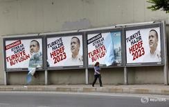 Женщина проходит мимо предвыборных плакатов Тайипа Эрдогана в Стамбуле 10 июня 2011 года. Спустя годы экономического роста, подогреваемого кредитами и внутренним потреблением, Турция столкнулась с увеличением безнадёжных долгов и банкротств компаний, которые оказывают давление на банки и хрупкую экономику страны, рискуя ослабить поддержку правящей партии.  REUTERS/Murad Sezer