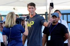 Michael Phelps speaks to the media after winning the men's 100-meter butterfly final during the Phillips 66 National Championships at Northside Swim Center. Mandatory Credit: Soobum Im-USA TODAY Sports