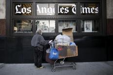 A homeless man reads the Los Angeles Times in the window of the building of Los Angeles Times newspaper, which is owned by Tribune Publishing Co, in Los Angeles, California, U.S., April 27, 2016. REUTERS/Lucy Nicholson