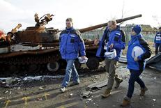 Deputy Chief of the Special Monitoring Mission of the Organization for Security and Cooperation in Europe (OSCE) to Ukraine Alexander Hug (L), with members of the mission, walks past a burnt tank as he inspects an area between self-proclaimed Donetsk People's Republic forces and Ukrainian government troops in the village of Kominternove north-east of the port city of Mariupol, Ukraine, January 15, 2016. REUTERS/Alexander Ermochenko - RTX22LAT