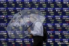 """Человек проходит мимо электронного табло с котировками в Токио 8 сентября 2015 года. Японский индекс Nikkei поднялся более чем на 2 процента, достигнув пиков полутора недель во вторник, после того, как министр финансов Японии сказал, что Токио пойдет на валютную интервенцию, если """"односторонний"""" рост иены сохранится. REUTERS/Issei Kato"""