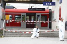 Сотрудники полиции на вокзале города Графинг-Мюнхен 10 мая 2016 года. Один человек погиб, еще трое пострадали в результате нападения вооруженного ножом мужчины на пассажиров, находившихся на железнодорожной станции под Мюнхеном во вторник утром, сообщили СМИ. Полиция выясняет, мог ли злоумышленник быть связан с радикальными исламистами. REUTERS/Michaela Rehle