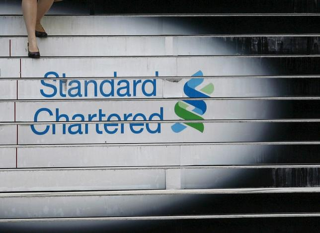 A woman walks down the stairs of the Standard Chartered headquarters in Hong Kong, October 13, 2010. REUTERS/Bobby Yip/File Photo