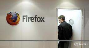 Мужчина проходит мимо логотипа браузера Firefox на Mobile World Congress в Барселоне 28 февраля 2013 года. Компания Mozilla Corp обратилась к федеральному судье с просьбой обязать правительство США раскрыть информацию об уязвимости её браузера Firefox, которая использовалась ФБР для отслеживания посетителей сайтов с детской порнографией. REUTERS/Albert Gea