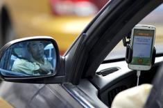 Un conductor se refleja en uno de los espejos laterales de un auto mientras usa la aplicación de transporte Didi Chuxing en Pekín, China, 22 de septiembre de 2015. Apple Inc anunció el jueves que invirtió 1.000 millones de dólares en el servicio de transporte chino Didi Chuxing, una decisión que según el presidente ejecutivo de la compañía estadounidense, Tim Cook, les ayudará a comprender mejor el importante mercado chino. REUTERS/Jason Lee