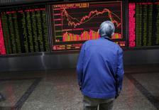 Un inversor mira un tablero electrónico que muestra la información de las acciones, en una correduría en Pekín, China, 15 de febrero de 2016. Las acciones chinas rebotaron el lunes después de que el regulador de valores local desmintió un reporte que dijo que suspendería la recaudación de fondos y las fusiones y adquisiciones en determinados sectores, lo que ayudó a contrarrestar unos decepcionantes datos económicos de abril. REUTERS/Kim Kyung-Hoon