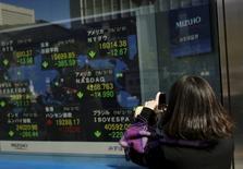 Una mujer toma fotografías de una pantalla que muestra varios índices de mercados. afuera de una correduría en Tokio, Japón. 10 de febrero de 2016. Las bolsas de Asia caían el miércoles luego de que datos revelaron una aceleración de la inflación en Estados Unidos y por los comentarios de unos funcionarios de la Reserva Federal que reavivaron las expectativas de un alza en las tasas de interés tan pronto como en junio. REUTERS/Thomas Peter