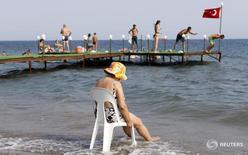 Туристы на пляже города Кючуккую, Турция 7 августа 2010 года. Британская туристическая компания Thomas Cook сообщила, что объем бронирования туров на летний период снизился на 5 процентов, поскольку туристы держатся в стороне от Турции, второго по популярности направления в прошлом году, в результате чего компании пришлось ухудшить прогноз прибыли на текущий год. REUTERS/Murad Sezer