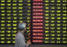 Инвестор смотрит на таблицу с котировками акция в брокерской компании в Наньцзине. Акции Китая выросли к закрытию торгов пятницы, однако индекс Shanghai Composite Index завершил в минусе пятую неделю кряду из-за ослабления оптимизма о перспективах роста экономики страны и опасений о повышении процентных ставок в США.  China Daily/via REUTERS