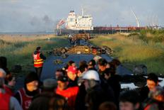 French workers and protesters walk near a barricade to block the entrance of the fuel depot of the society SFDM near the oil refinery of Donges, France, May 23, 2016. REUTERS/Stephane Mahe