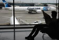 Пассажир читает газету в зале вылета аэропорта Хитроу в Лондоне; за окном виден лайнер авиакомпании EgyptAir. Фото от 20 мая 2016 года. Анализ останков жертв крушения самолета EgyptAir указывают на взрыв на борту, хотя следов взрывчатки не обнаружено, сообщили во вторник представитель египетских судмедэкспертов и источники, связанные с расследованием. REUTERS/Yannis Behrakis