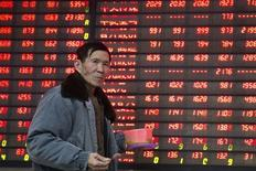 Un inversor camina junto a un tablero electrónico que muestra información bursátil, en una correduría en Nanjing, provincia de Jiangsu, China. 14 de enero de 2016. Las acciones chinas cerraron a la baja el martes luego de que las empresas de recursos básicos se vieron afectadas por una caída en los precios de las materias primas en medio de las preocupaciones sobre la salud de la economía de China. REUTERS/China Daily