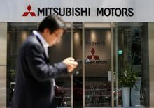 A man walks in front of an entrance of Mitsubishi Motors Corp's headquarters in Tokyo, Japan, May 13, 2016. REUTERS/Issei Kato