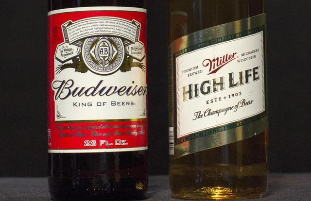 A bottle of Budweiser and a bottle of Miller High Life are pictured together in this photo illustration in the Manhattan borough of New York October 14, 2015. REUTERS/Brendan McDermid/Files