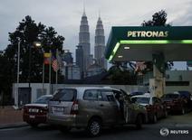 Такси на заправке Petronas в Куала-Лумпуре 10 февраля 2016 года. Малайзийская государственная нефтегазовая корпорация Petroliam Nasional Berhad сообщила в среду, что не обсуждала с российскими компаниями продажу каких-либо из своих активов или доли. REUTERS/Olivia Harris