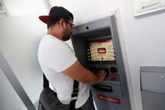El estudiante mexicano Kevin, de 20 años, retira dinero de un cajero automático que le envió su madre que vive en Estados Unidos, en Ciudad de México. 31 de marzo de 2016. REUTERS/Edgard Garrido