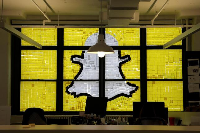 An image of the Snapchat logo created with Post-it notes is seen in the windows of Havas Worldwide at 200 Hudson Street in lower Manhattan, New York, U.S., May 18, 2016, where advertising agencies and other companies have started what is being called a ''Post-it note war'' with employees creating colorful images in their windows with Post-it notes. REUTERS/Mike Segar